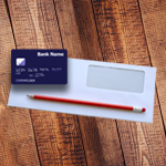 Credit card, envelope and pencil on a wooden table.